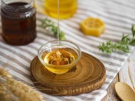 delizioso miele che versa nella ciotola di vetro, primo piano foto