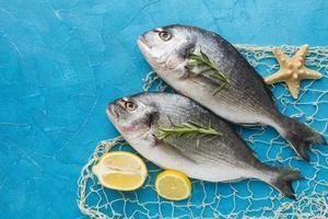 disposizione di pesce con limone su sfondo blu, vista dall'alto foto