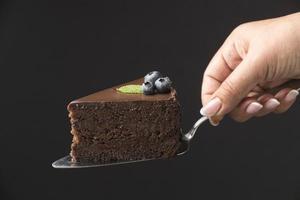 vista frontale della mano che tiene la fetta di torta al cioccolato foto
