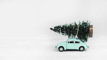 giocattolo auto con abete in cima su sfondo bianco foto