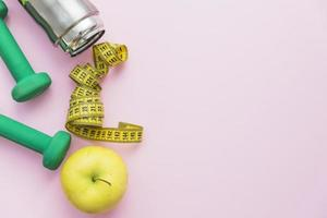 manubri, bottiglia d'acqua, metro a nastro e una mela su sfondo rosa foto