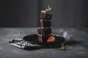 vista frontale della torta al cioccolato impilati su un piatto nero con menta, messa a fuoco selettiva foto