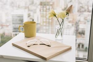 un libro di occhiali da vista vicino a fiori e tazza sul tavolino della finestra foto