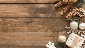 confezione regalo con palline lucide e pigne su fondo in legno foto