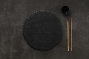 piatto rotondo in pietra con bacchette foto