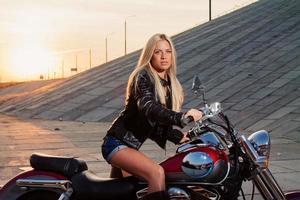 bionda sexy che si siede sulla sua moto foto