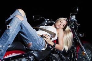 bionda sexy sdraiata sulla sua moto foto