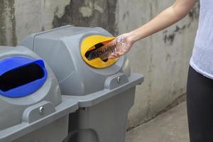 Stretta di mano della donna gettando la bottiglia di plastica vuota cadere in un cestino, salva il concetto di mondo foto
