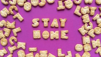 stare a casa. citazione di quarantena da cracker su sfondo rosa e lettere sparse. semplice piatto laici con texture pastello. fotografia stock.