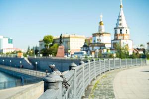 Piccione su una rotaia di cemento accanto a un corpo idrico a Irkutsk, Russia foto
