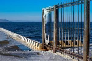 ghiaccio su una recinzione metallica accanto a un corpo idrico foto
