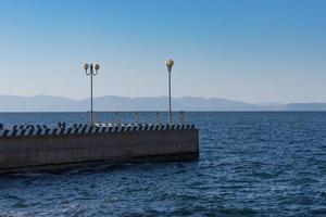 vista sul mare a un molo con lampioni a vladivostok, russia foto