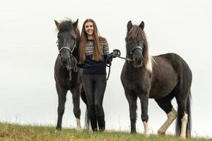 giovane donna in piedi in un campo con i suoi due cavalli islandesi neri foto