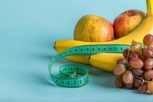 frutti maturi e nastro di misurazione su sfondo blu. il concetto di dieta e corretta alimentazione. foto