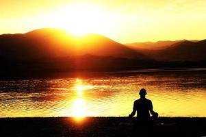 sagoma di un uomo che medita su una riva del lago foto