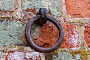 vecchio anello di ferro montato in un muro di mattoni foto