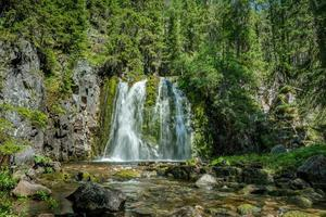 cascata che abbatte una parete rocciosa coperta di muschio verde foto