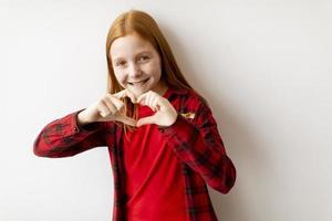 ragazza carina con i capelli rossi in piedi vicino al muro bianco e che mostra la forma del cuore con le dita foto