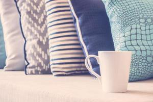 tazza di caffè bianco sul divano con decorazione cuscino foto