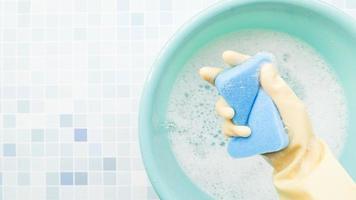 mano che tiene una spugna blu per la pulizia foto