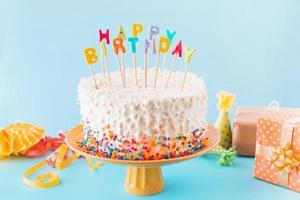 torta di compleanno con accessori regalo su sfondo blu foto