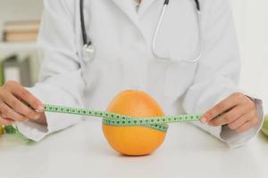 nutrizionista di primo piano che misura un'arancia, concetto foto