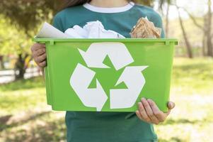 donna del primo piano che tiene un cestino di riciclaggio in natura foto