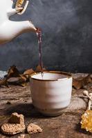 vista frontale del tè che viene versato in tazza foto