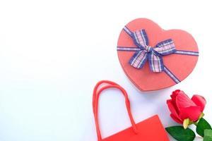 vista dall'alto di una confezione regalo a forma di cuore e rosa su sfondo bianco foto