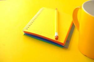 blocco note giallo con matita e tazza foto