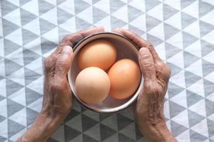 mani che tengono una ciotola di uova foto