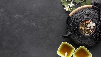 tè essiccato e ingredienti a base di erbe con teiera nera su sfondo di pietra ardesia foto