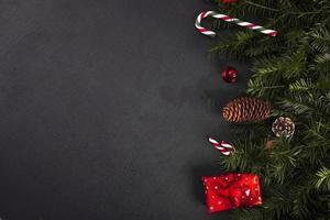 ramoscelli di abete vicino a bastoncini di zucchero e confezione regalo foto