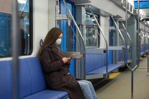 una donna con una maschera è seduta e utilizza uno smartphone in un moderno vagone della metropolitana foto