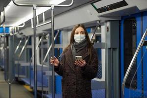 una donna con una maschera è in piedi e utilizza uno smartphone in un moderno vagone della metropolitana foto