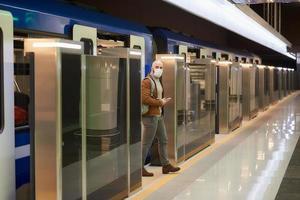 uomo con una maschera medica è in possesso di un telefono mentre lascia un moderno vagone della metropolitana foto