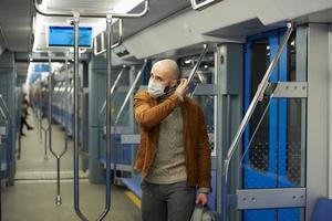 un uomo con la barba si sta mettendo una maschera medica in un vagone della metropolitana foto