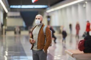 un uomo con una maschera facciale sta usando uno smartphone mentre aspetta un treno della metropolitana foto