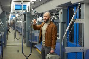 un uomo con la barba si toglie una maschera medica e sorride su un treno foto