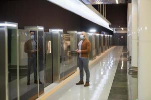 un uomo con una maschera facciale tiene in mano uno smartphone mentre aspetta un treno della metropolitana foto