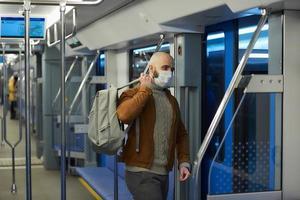 un uomo calvo con la barba in una maschera facciale si sta mettendo uno zaino in un vagone della metropolitana foto