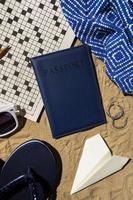 passaporto e accessori da viaggio sulla sabbia foto
