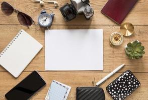 copia spazio con telefono, fotocamera e bussola sulla scrivania foto