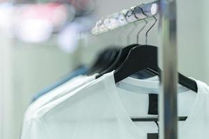 Close up di magliette bianche su grucce, sfondo di abbigliamento foto