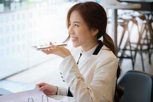 donna che parla al telefono con altoparlante in ufficio foto