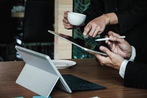 gestori di fondi che consultano e discutono analisi, investimenti nel mercato azionario tramite tavoletta digitale. foto
