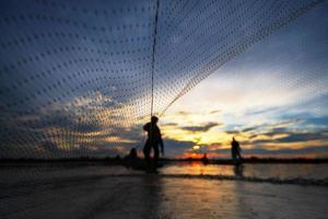 silhouette del pescatore sulla barca da pesca con rete sul lago al tramonto, Thailandia foto