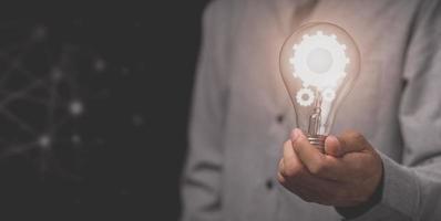 la mano di un uomo d'affari tiene una lampadina e ha un'icona a forma di ingranaggio foto