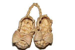 due scarpe di rafia di vimini legate insieme su uno sfondo bianco foto