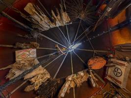 vista interna, guardando in alto, di un tepee con abiti tradizionali in pelle e contenitori in pelle grezza foto